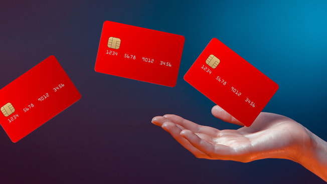 Hand floating in a space with three credit cards floating out of the hand.