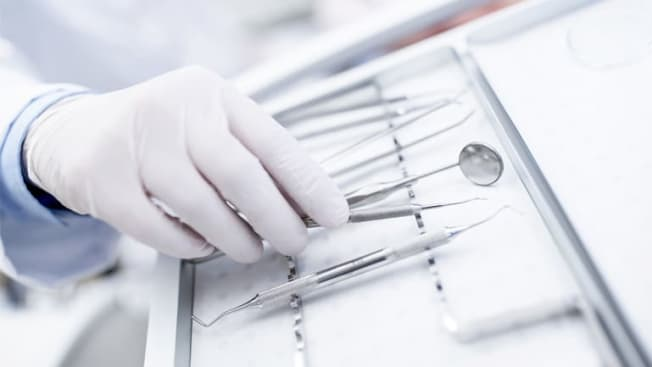 Dentist with dental tools in dentist office
