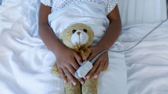 A child of color in a hospital bed with a teddy bear