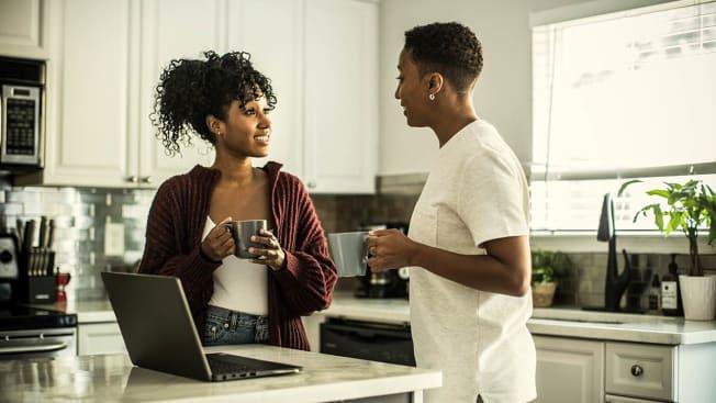A Black couple speaking in their kitchen.