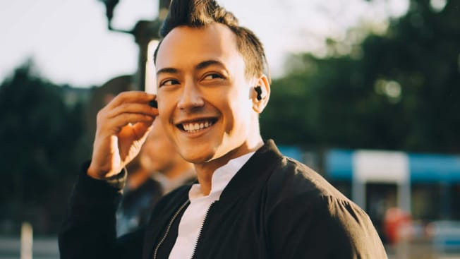 Person smiling with earbuds in their ears