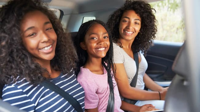 three kids of various ages wearing seatbelts in backseat of car