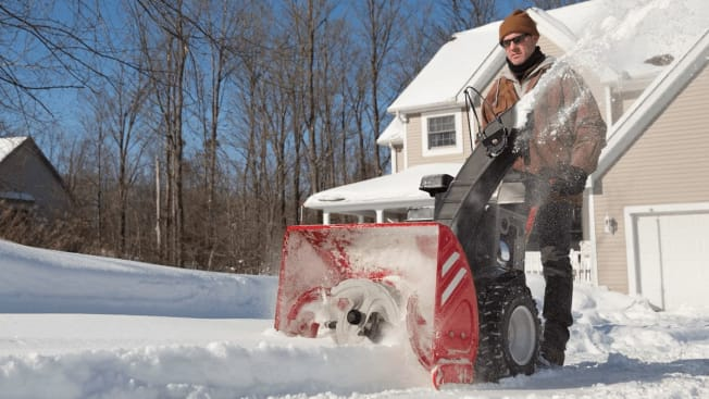 Person using a three-stage snow blower to clear snow