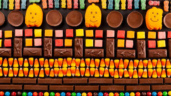 various candies lined up in graphic pattern (Sour Patch Kids, Reese's, Pumpkin Peeps, candy corn, Kit Kat, M&M's, Snickers, Starburst)