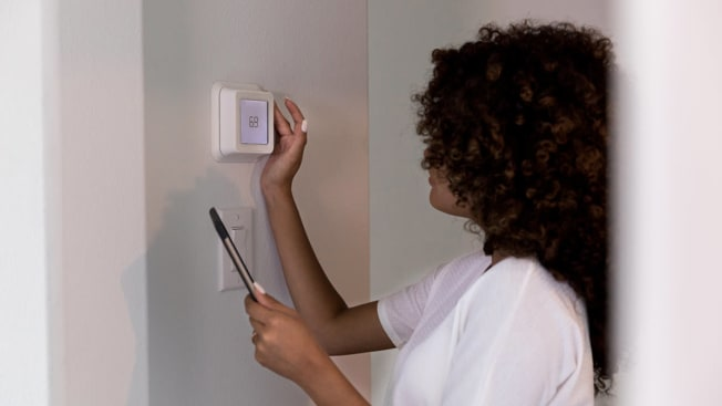 woman using smart thermostat in the home