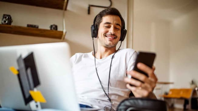 person wearing wired headphones while in front of computer and looking at phone