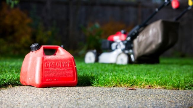 gasoline can on pavement with lawn mower in background