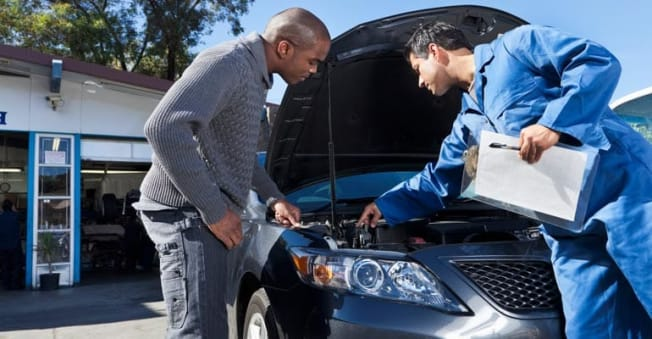 Mechanic looking at car engine.