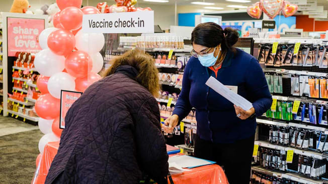 A worker checks in a person with an appointment to receive a dose of the Moderna Covid-19 vaccine at a CVS Pharmacy location in Eastchester, New York,