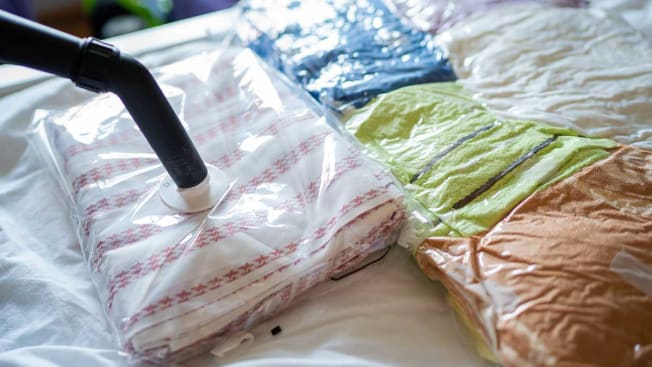 A person vacuum sealing bags of clothing using the hose of a vacuum.