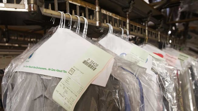 Clothing wrapped in plastic hanging at a dry cleaner.