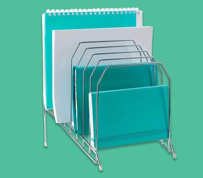Metal file organizer with papers and notebooks sitting in its slots.