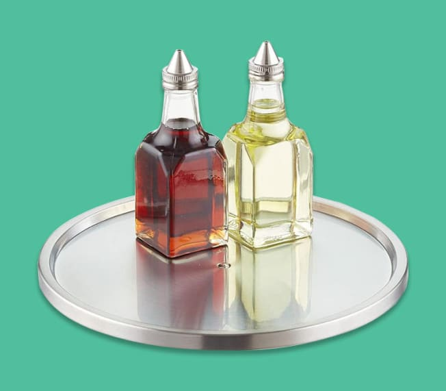 Metal lazy susan with oil and vinegar bottles sitting on top of it.