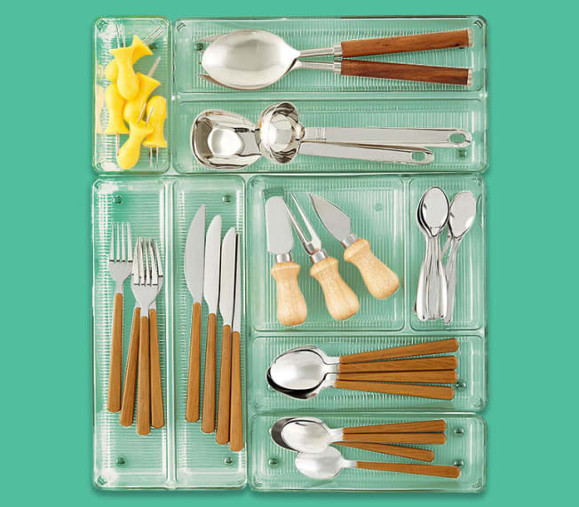 Shallow plastic containers in various sizes filled with cutlery.