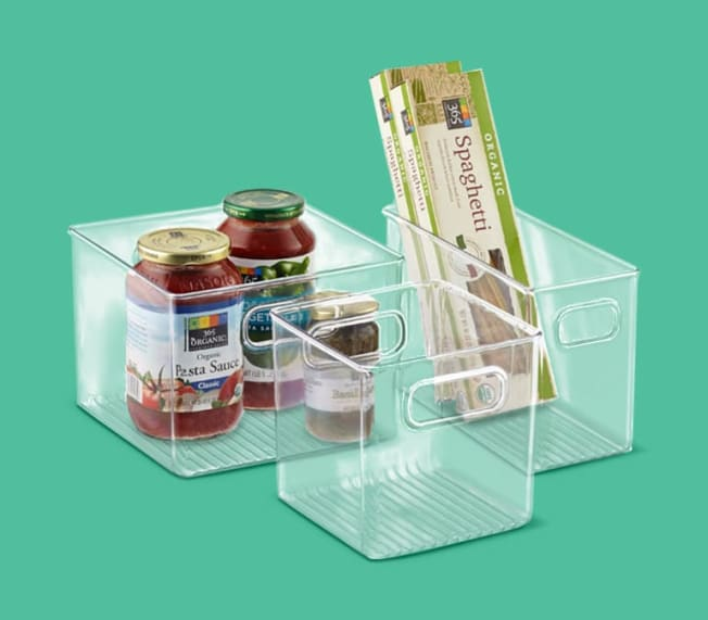 Different sized plastic bins with pantry items sitting inside them.