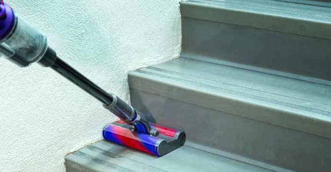 cleaning corner of stairs with handheld vacuum
