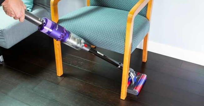 handheld vacuum being pushed under chair on wooden floor