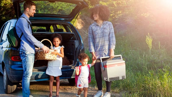 Family with two children getting out of their car holding a picnic blanket and a cooler.
