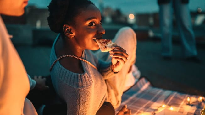 A person leaning on a picnic blanket eating food by candlelight.