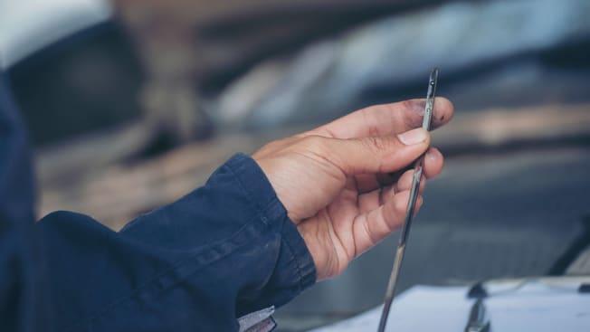 Person checking a car's dipstick.