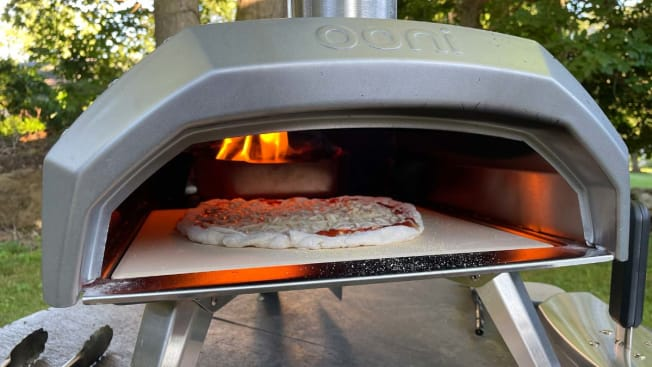 A pizza being cooked inside the Ooni Pizza Oven.