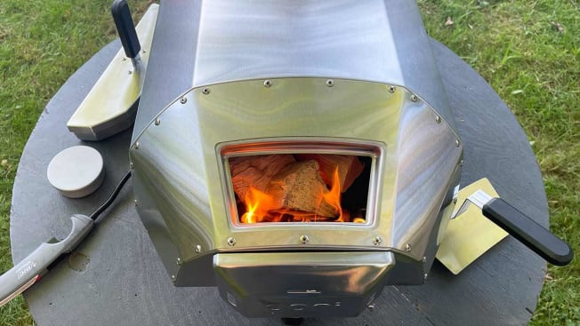 A view of the back of the Ooni pizza oven with fire visible in the opening intended for firewood placement.