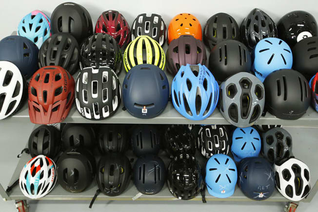 cart with various colors and models of bike helmets