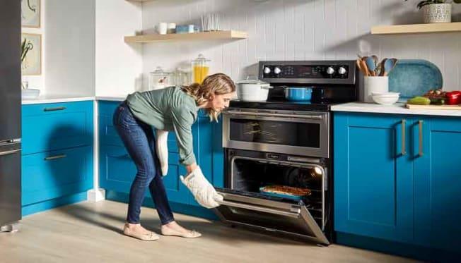 person wearing oven mitt closing bottom door to range