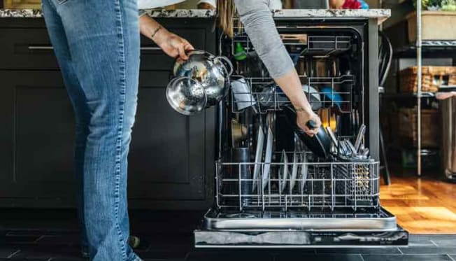 person loading dishwasher with dirty dishes