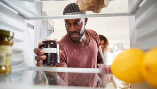 person taking jar of jelly out of refrigerator