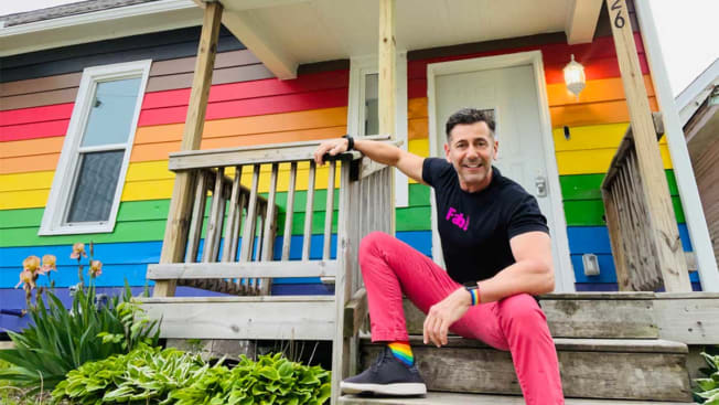 Robert Geller sitting on the front steps of a house painted with rainbow stripes.