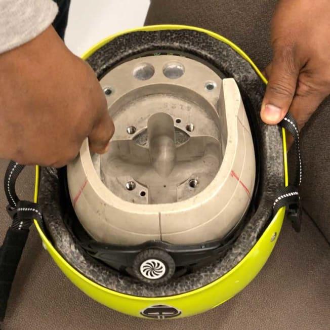 technician putting helmet into headform for helmet testing