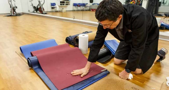 technician pushing hand on yoga mat for test