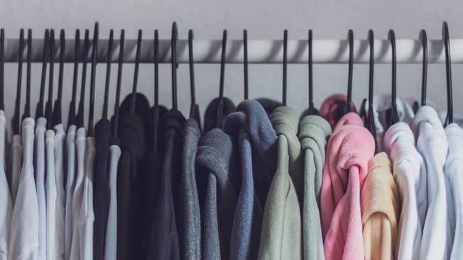 Close up of multiple clothing items hung up on hangers
