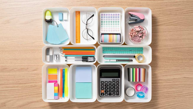 Various office supplies organized in little plastic containers