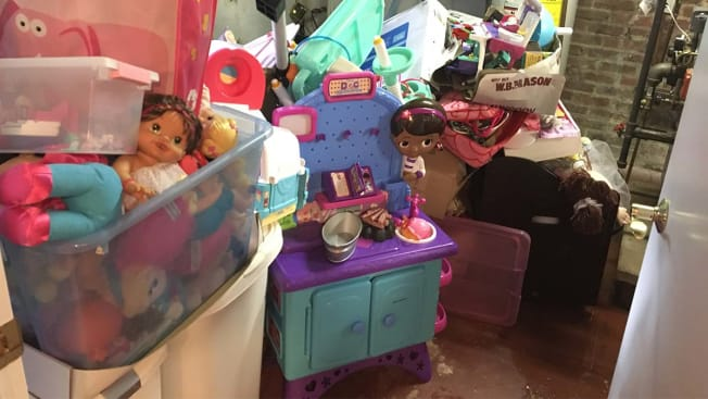 Toys stacked in plastic boxes in flooded basement