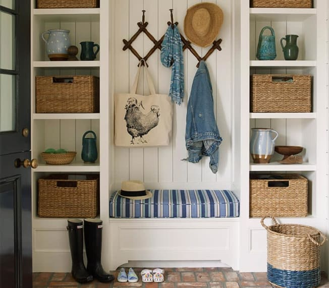 Entryway with large bench with storage and children's accessories.