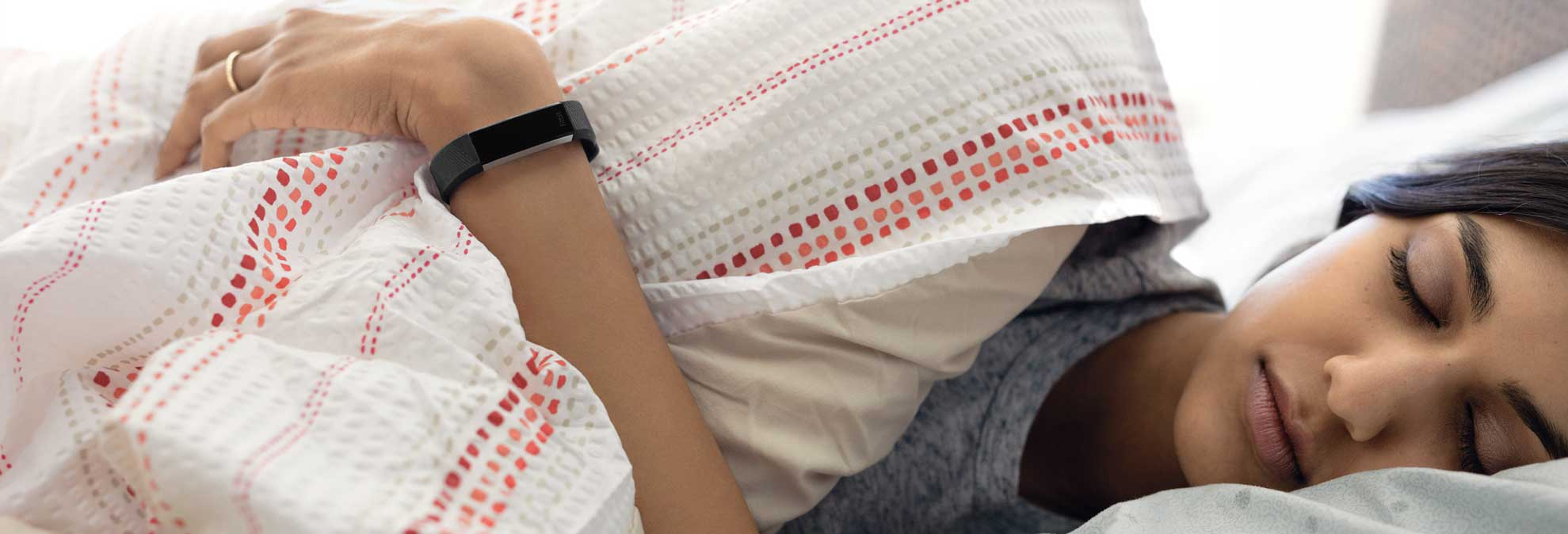 A woman wearing a fitness tracker sleeping