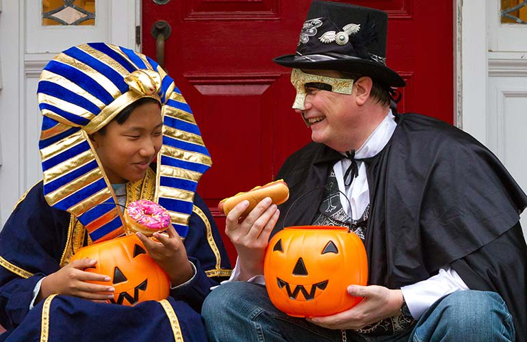 A son dressed as a pharaoh and a dad dressed as a magician in a Halloween photo