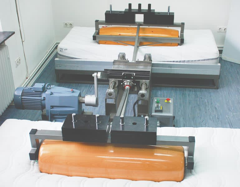 Image from CR's mattress tests where a roller is used to simulate wear.