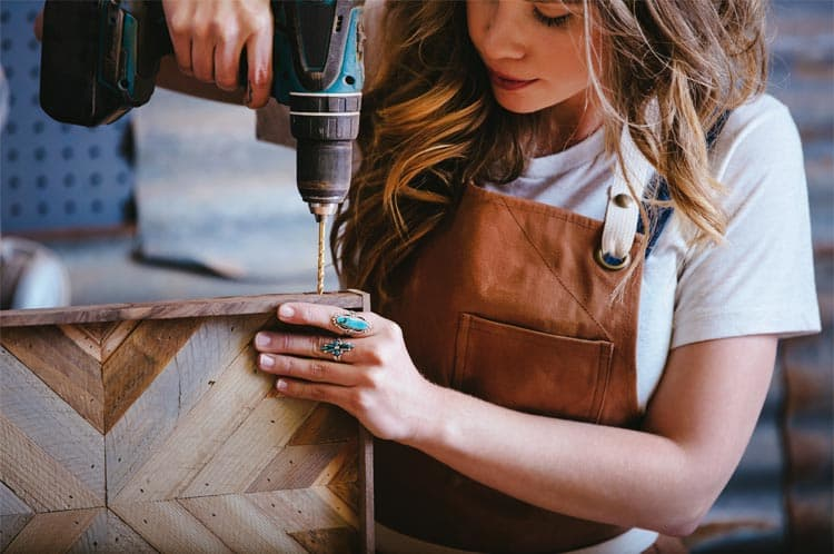 A woman using a cordless drill while working on a piece of wood furniture.