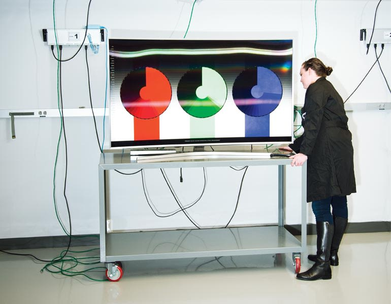 A TV tester wheeling a 4K HDR TV into a CR TV lab.