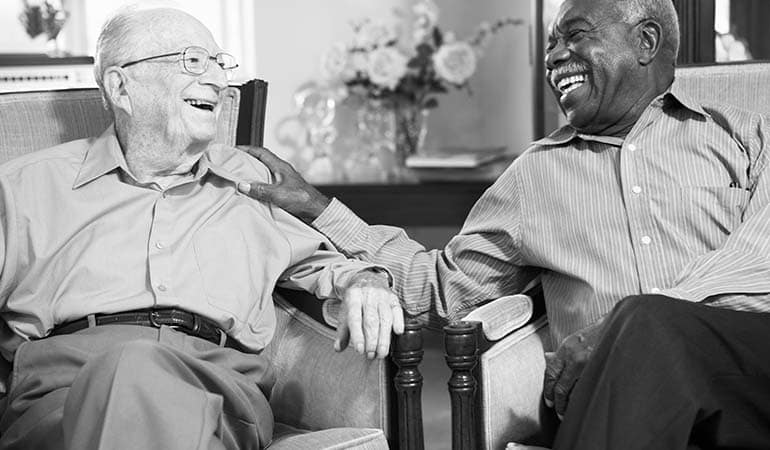 Two elderly men laughing together
