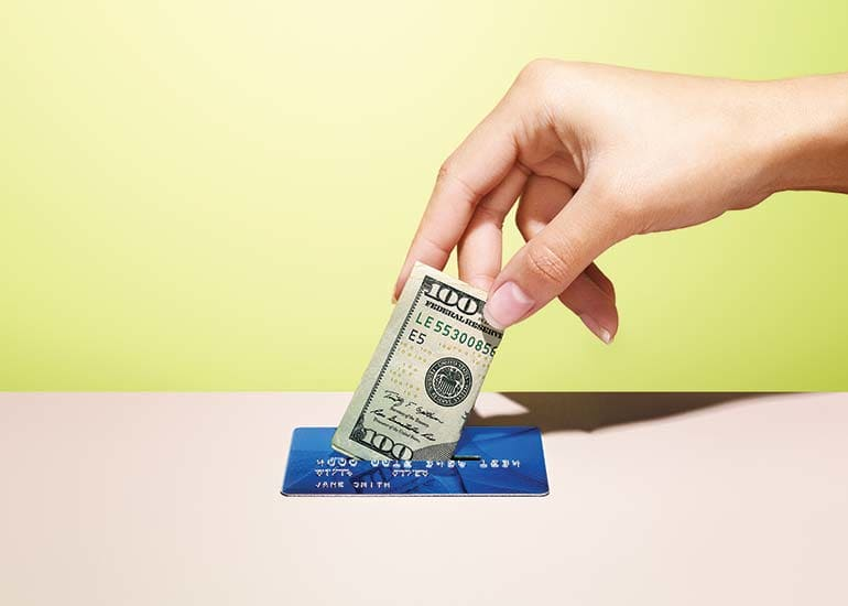 An image of cash and a credit card to illustrate how cash-back credit cards can earn you money.