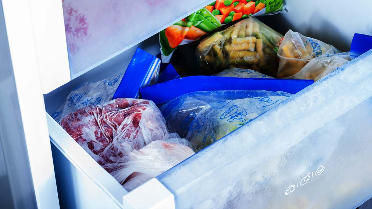 A freezer storage bin filled with frozen foods.