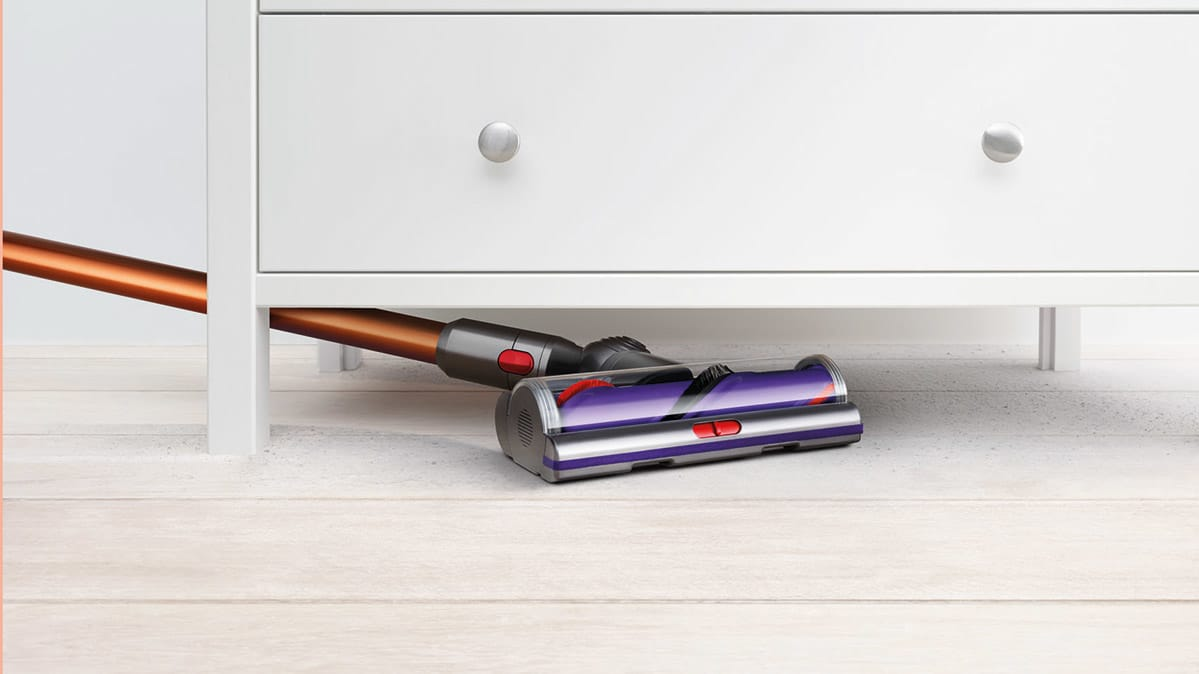 The Dyson Cyclone V10 vacuuming under a dresser.