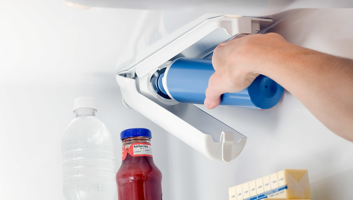 A person installs a replacement refrigerator water filter.