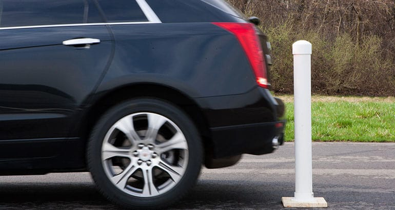 A Cadillac backing into a pole to illustrate rear crash-prevention technology
