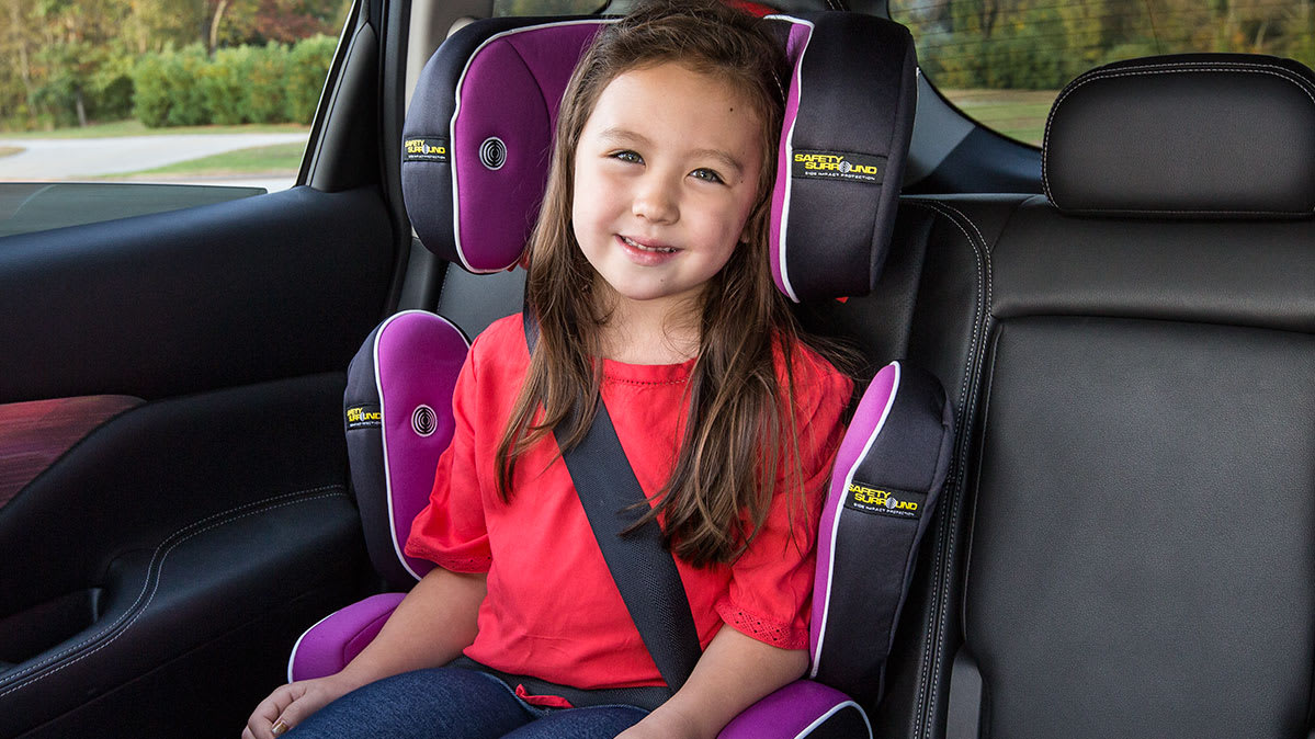 A young girl in a booster seat.