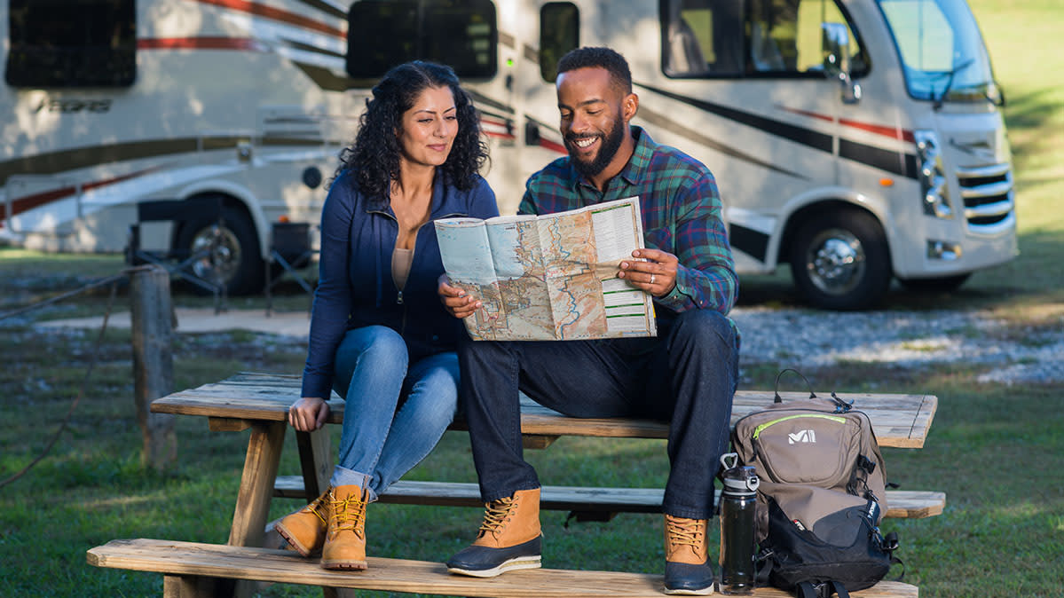 A couple sitting in front of an RV.
